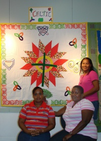 Jamaican students standing in front of quilt