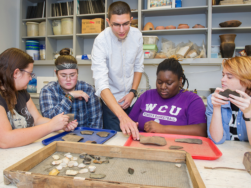 Anthropology students studying remains from field experiences
