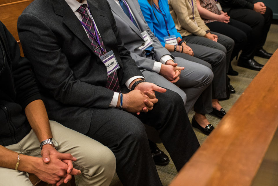 Students sitting in a courtroom with their hands in their laps