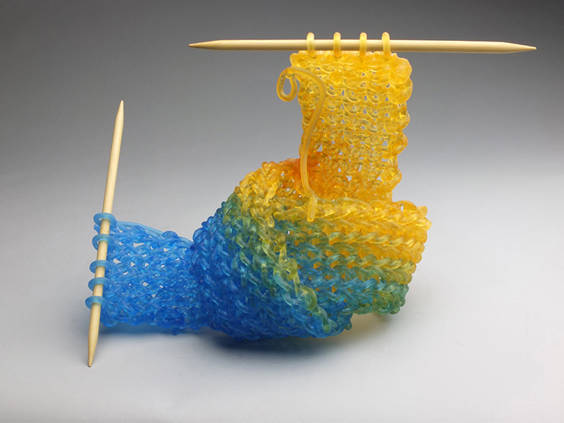 Carol Milne, Knit Knot, 2014, kiln-cast lead crystal knitted glass and needles, 10 x 15 x 8 inches, Collection of the Asheville Art Museum, Image courtesy of the Artist