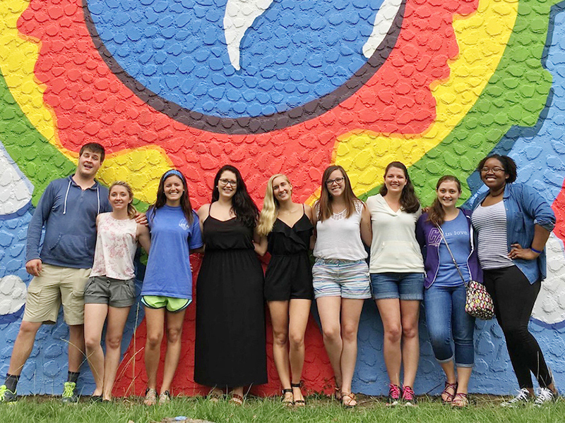 Humanties Students in front of a multicoloured wall.