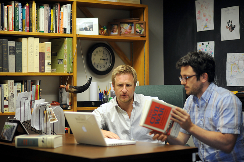 Two men discussing history research in an office
