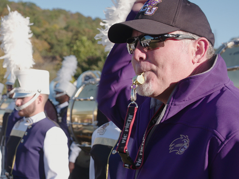 Band director blows whistle for band.