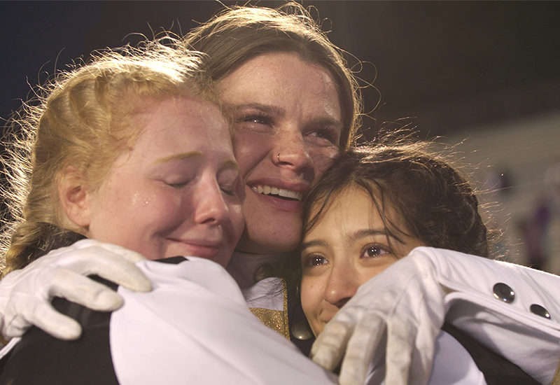 Band students embrace one another.