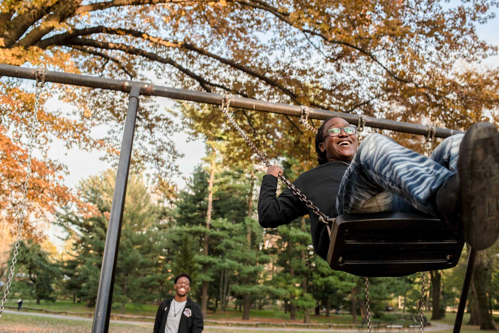 Student swings on swing set in Central Park.