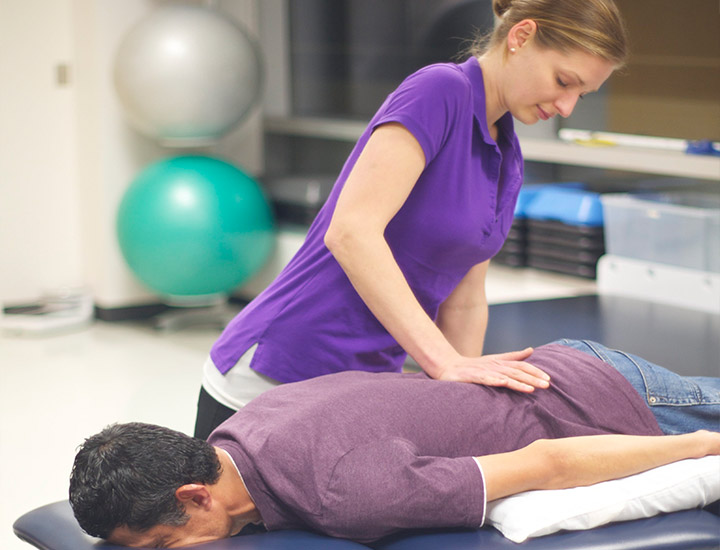 Student performing lumbar mobilizations for patient