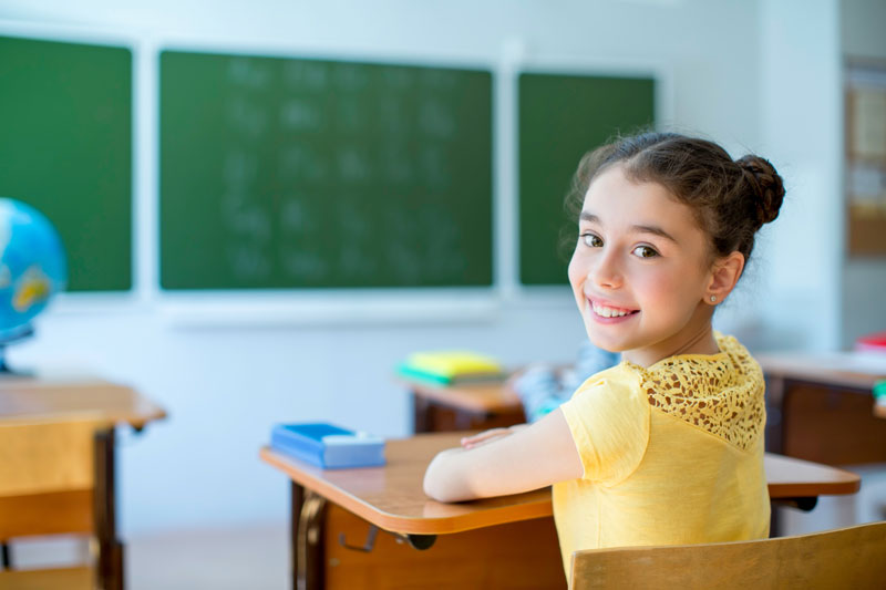 Young girl at desk in classroom