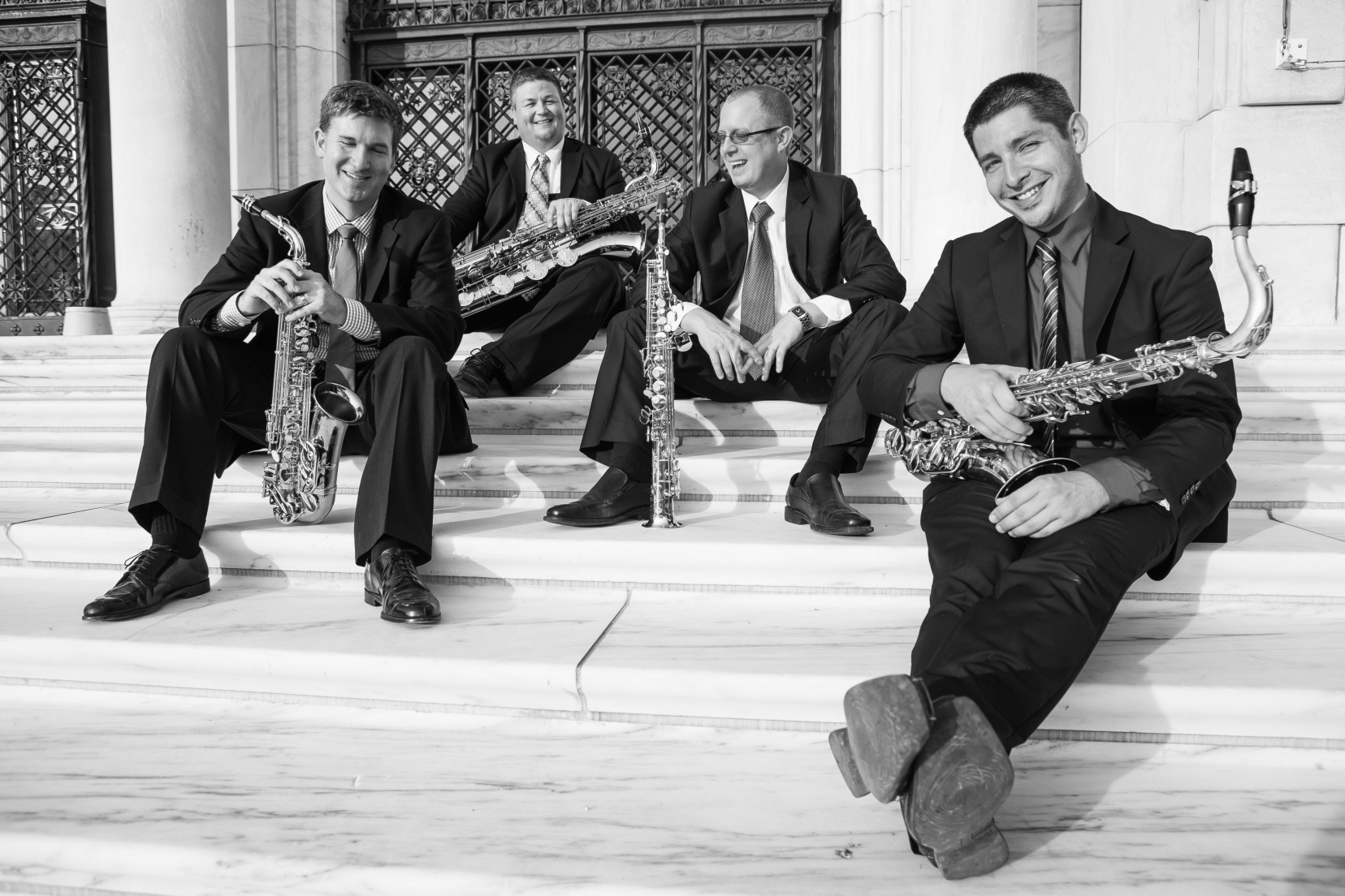 Men sitting on steps with saxophones