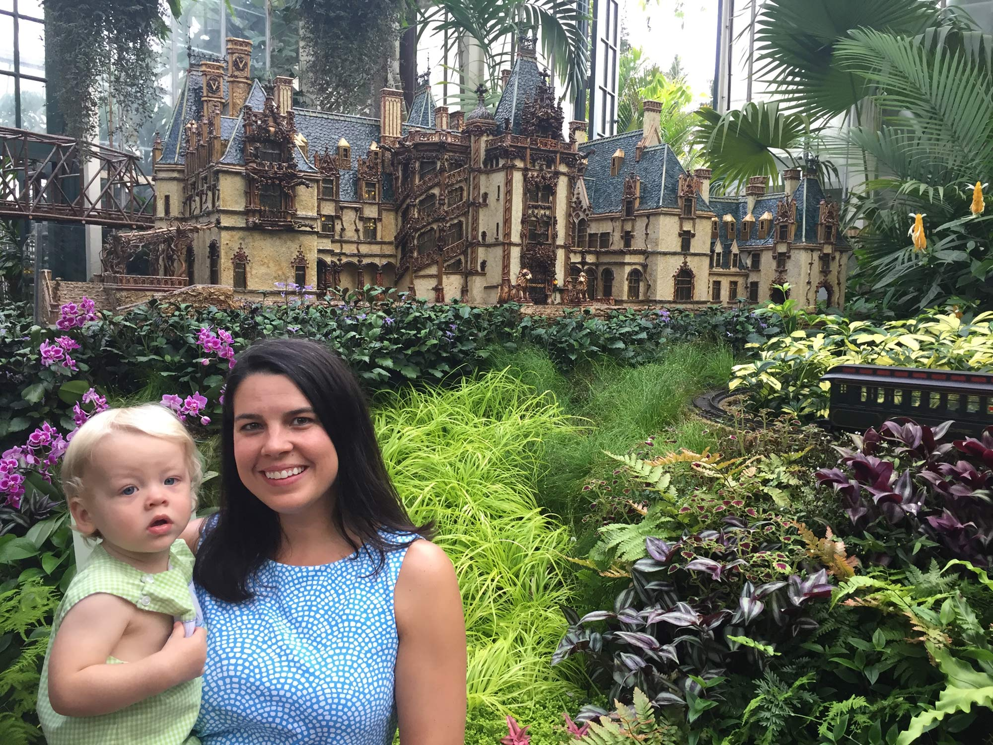 Michaela Schmidlin, MPM '18, and son William at the Biltmore Gardens Railway exhibit. William was born while Michaela was completing the program.