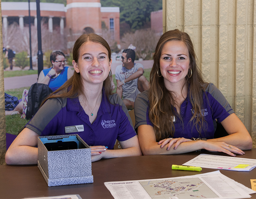 Orientation Counselors at a table ready to greet potential Catamounts!