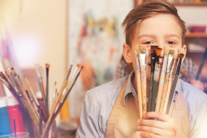 Boy holding paint brushes in front of face