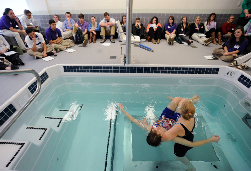 Class of students learning at the therapy pool