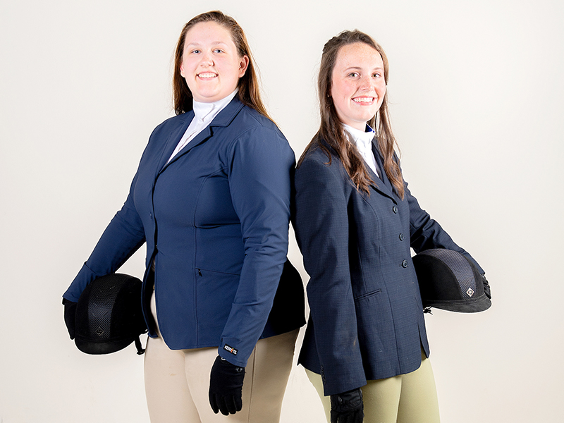 two female students pose for the camera while wearing their equestrian outfits and holding helmets