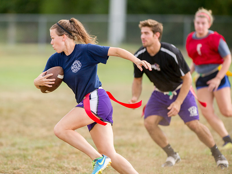 female student running while clutching a football
