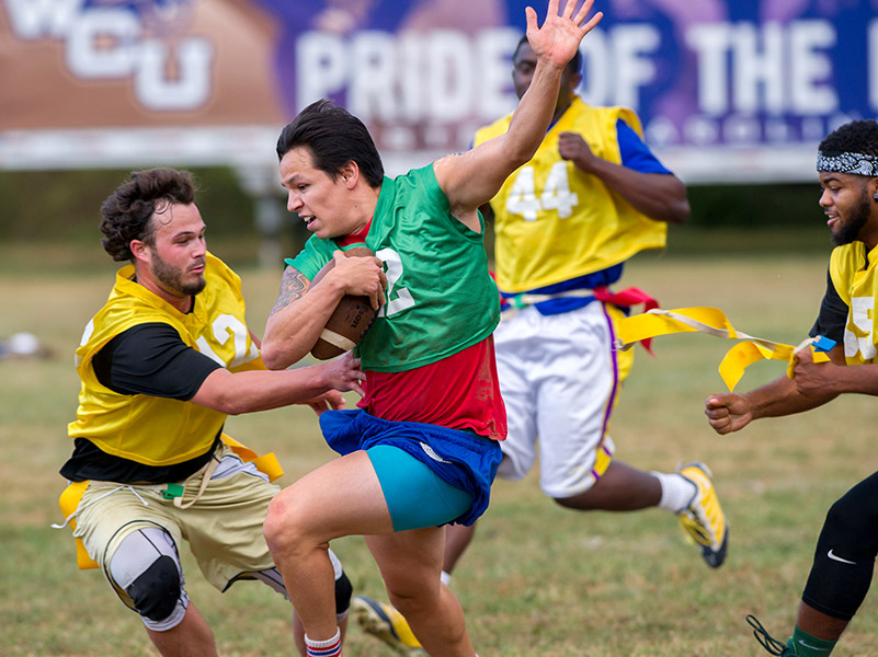 male students running dodging each other in flag football game