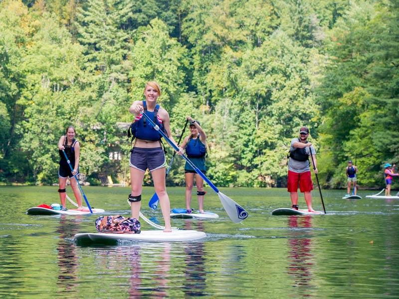 students smile as they paddle around on stand up paddleboards at a local lake