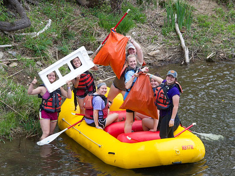 a group of students in a river raft hold up trash they have collected from the river