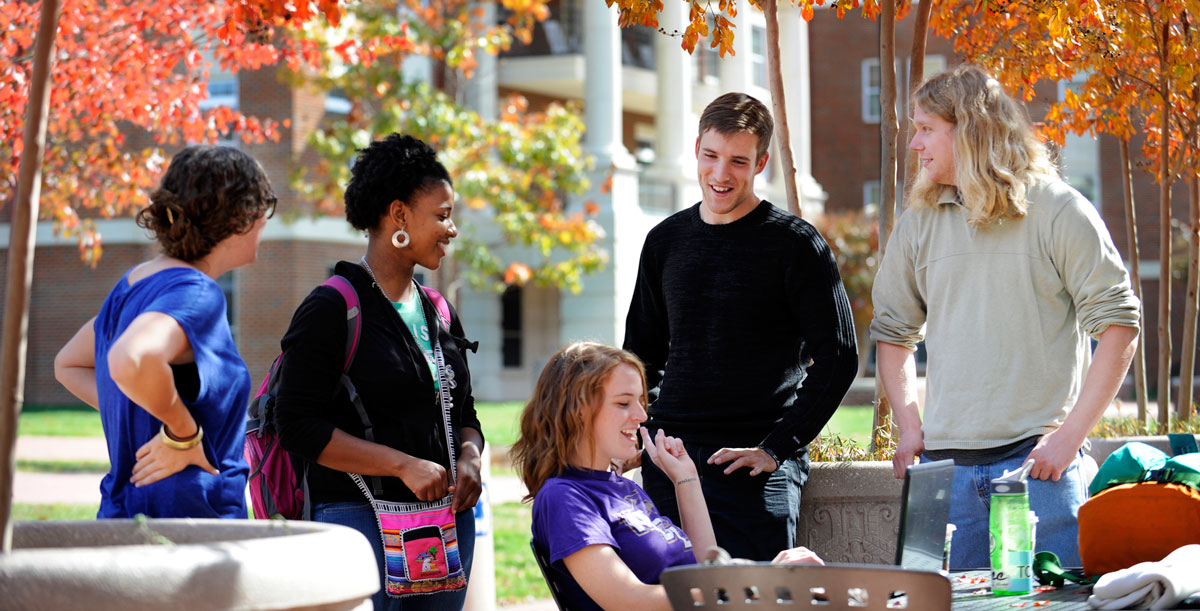 students talking around laptop