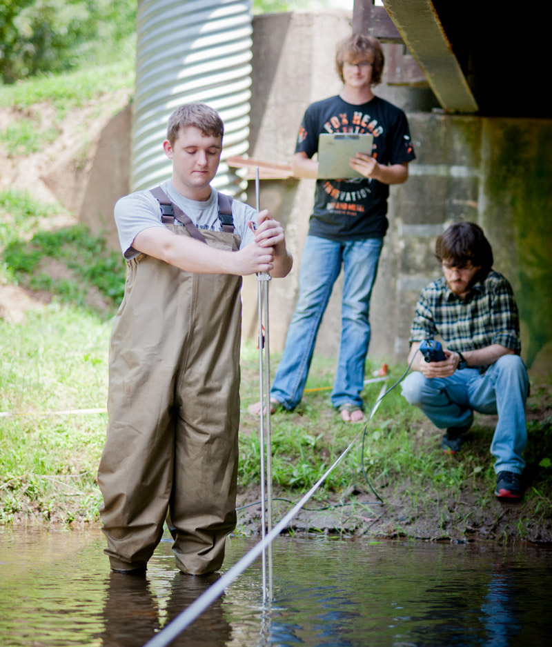 Graduate Students researching in a creek