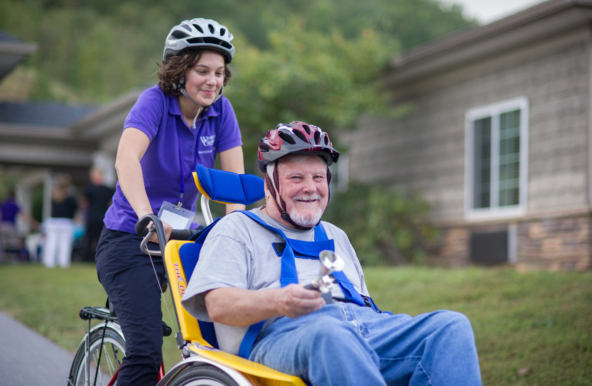 Recreational therapy student giving an elderly man a bicycle ride