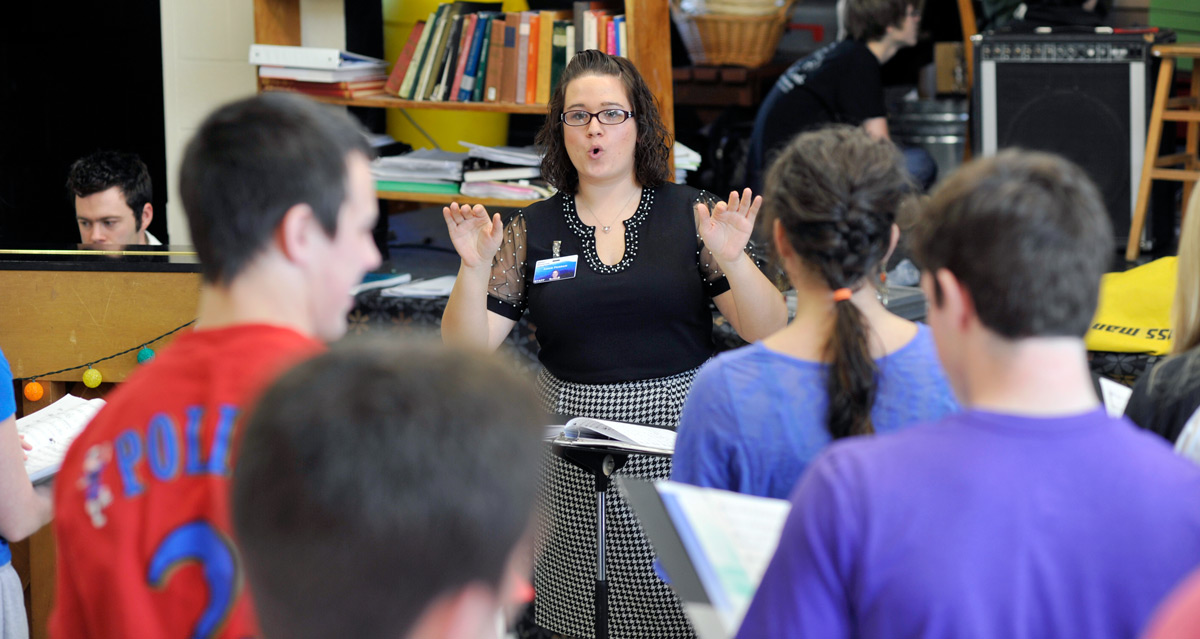 Student teacher directing in a high school chorus classroom