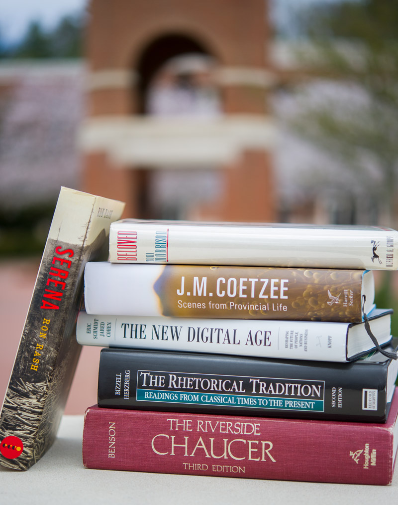 Stack of classic books in front of the Alumni Tower