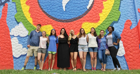 group of students posing in front of world mural