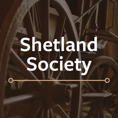 "A sepia toned photograph of a wagon wheel with white text stating ""Shetland Society"""