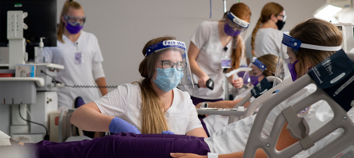Photo of students working in a nursing lab