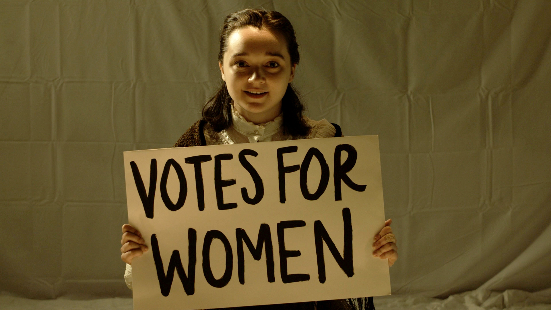Screenshot of a woman with a sign that says 'votes for women'